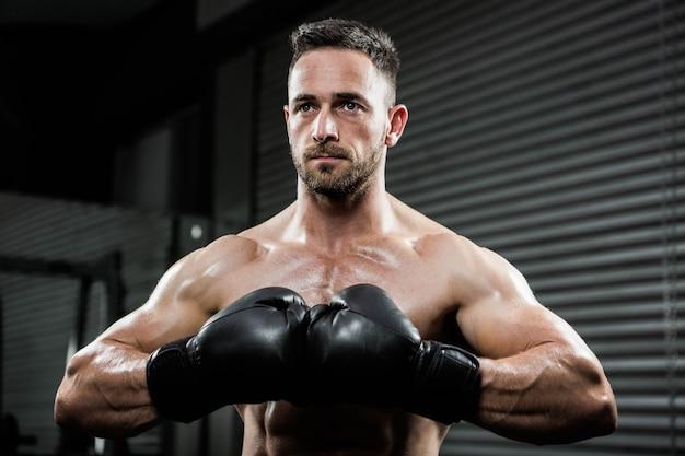 Crossfitジムでボクシンググローブを持つ上半身裸の男を決定