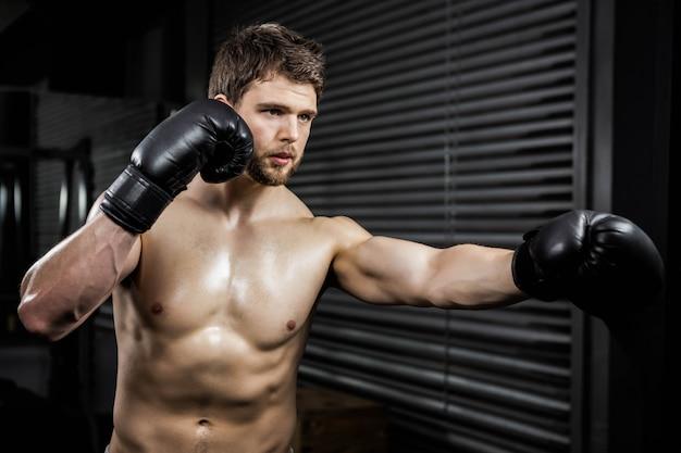 Crossfitジムでボクシンググローブのトレーニングを持つ上半身裸の男