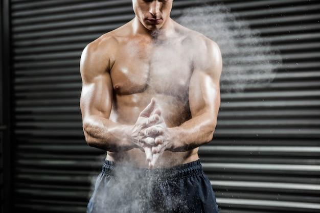 Мужчина без рубашки хлопает в ладоши с тальком в тренажерном зале crossfit