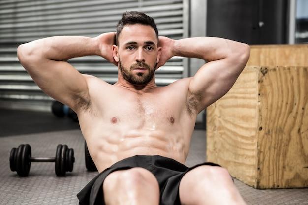 Crossfitジムで腹部のクランチをしている上半身裸の男