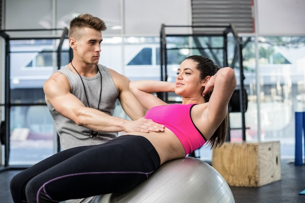 Crossfitジムで腹筋を持つ女性を支援する男性のトレーナー