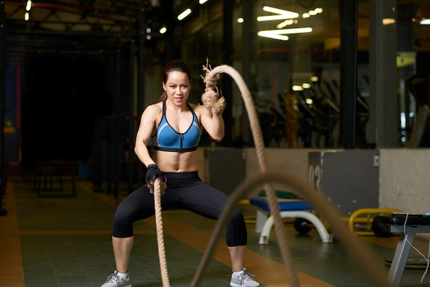 Упражнение crossfit в исполнении сильной женщины с веревкой