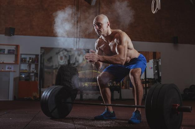 重いバーベルを行使する強い男性crossfitアスリート