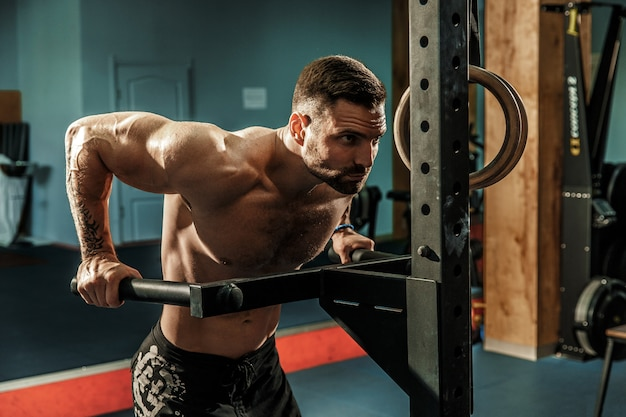 Сильный мускулистый мужчина, делать отжимания на брусьях в тренажерном зале crossfit