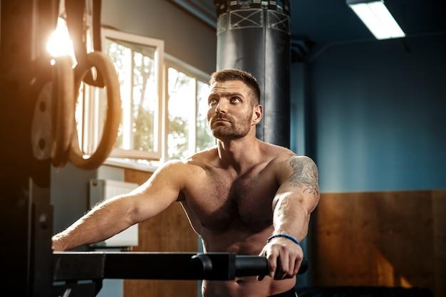 Crossfitジムでのトレーニングの準備をしている強い男