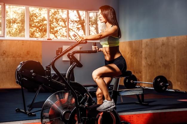 Женщина фитнеса используя воздушный велосипед для кардио тренировки в спортзале crossfit.
