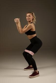 Crossfit健康的なライフスタイルのコンセプト。素敵な魅力的な愛らしい美しいスポーティなフィットネスモデルの女性の脚にピンクのゴムバンド付きのスポーツ服を着ています。