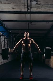強い男のワークアウトによるcrossfitフィットネスジム重量挙げバー