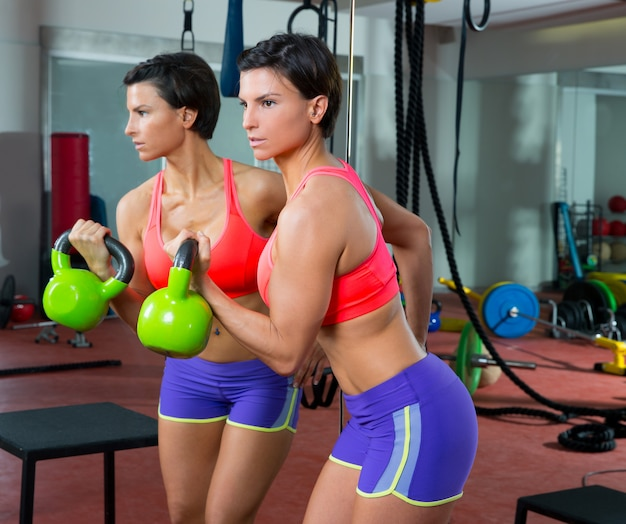 Crossfitフィットネスミラートレーニングでケトルベル女性を持ち上げる
