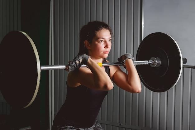 Сильная женщина поднимает штангу как часть рутины тренировки crossfit