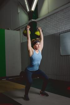ケトルベルによるフィットネス女性トレーニング。 crossfit運動をしている若い女性に合います。