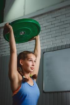 ジムで体重crossfitを持ち上げる筋肉の若いフィットネス女性。クロスフィット