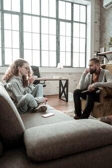 足を交差させます。ソファに座ってセラピストと話している彼女の足を組んで、巻き毛の黒髪の 10 代