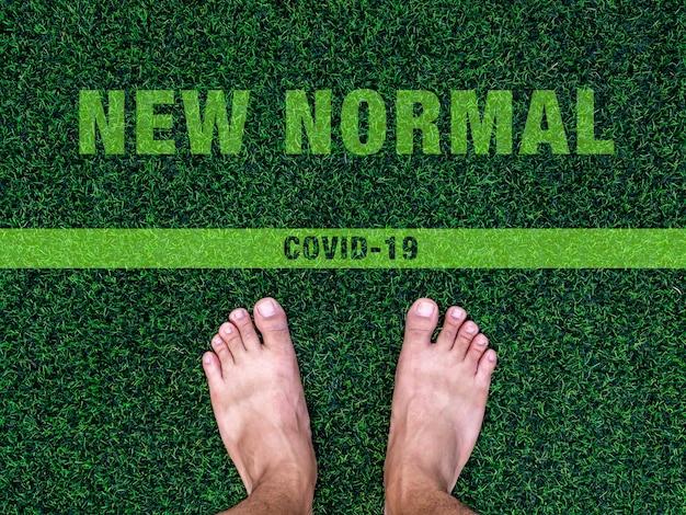 ニューノーマルのコンセプトへのクロス。 covid-19コロナウイルスのパンデミック状況のコンセプトの後、「ニューノーマル」というテキストと線が付いた人工の緑の芝生の上の裸足。