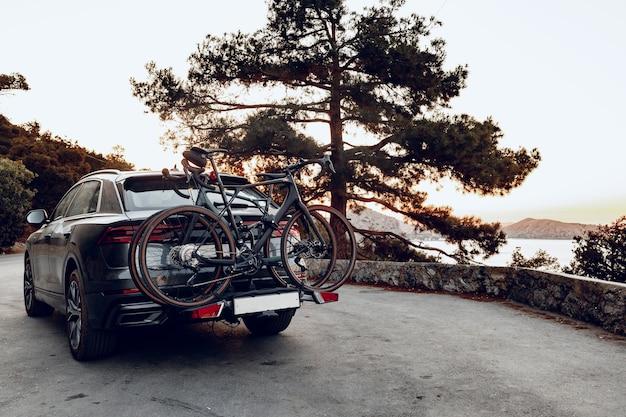 沿岸道路に駐車されたラックにロードされた2つのロード自転車を備えたクロスオーバー車