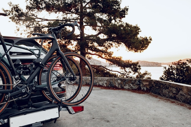 沿岸道路に駐車したラックに2台のロードバイクを積んだクロスオーバーカー