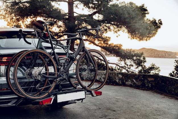 Кроссовер с двумя дорожными велосипедами, загруженными на стойку
