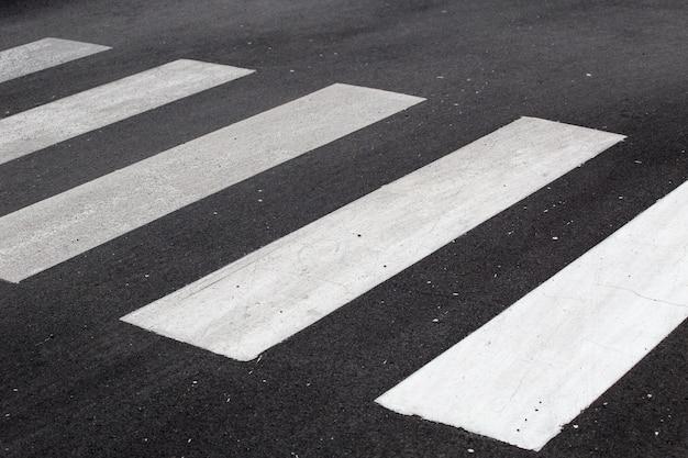 Crosswalk on black asphalt road.