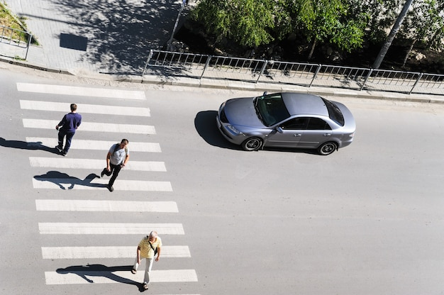 Crosswalk. top view. ivano-frankivsk. ukraine-23.05.2017. people are crossing a street. a car is waiting for pedestrians.
