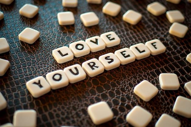「自分を愛する」というフレーズを構成するクロスワードゲームの駒