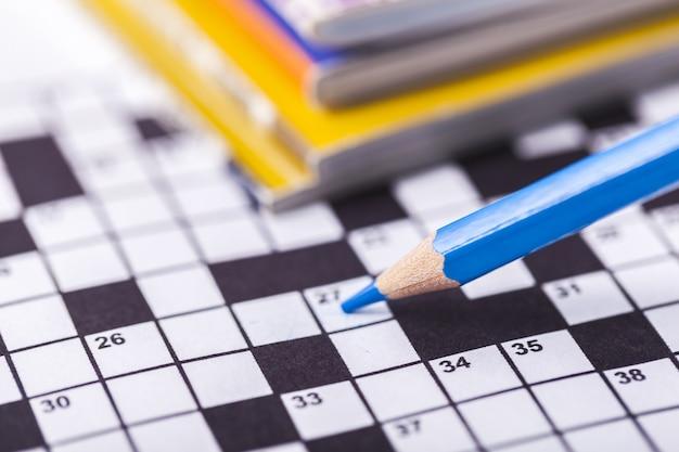 背景のクロスワードパズルと鉛筆