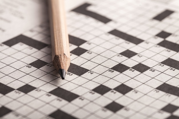 Crossword puzzle and pencil on background