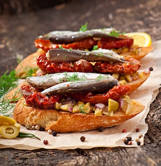 Кростини с анчоусами, оливками и вялеными помидорами