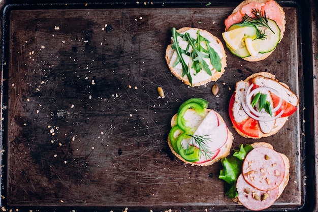 Crostini with different toppings on black table background.