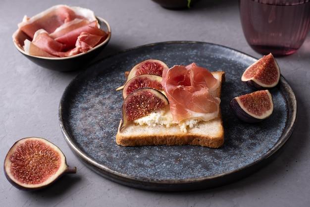 イタリアのハムとリコッタチーズのクロスティーニ、生ハムとイチジクのトースト、暗い背景、クローズアップ。