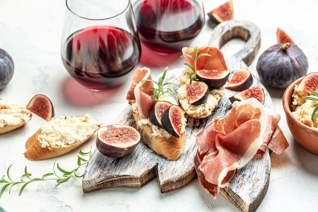 프로슈토, 크림 치즈, 무화과, 레드 와인을 잔에 넣은 크로스티니. 전통적인 스페인 타파스 세트입니다. 음식 조리법 배경입니다. 확대