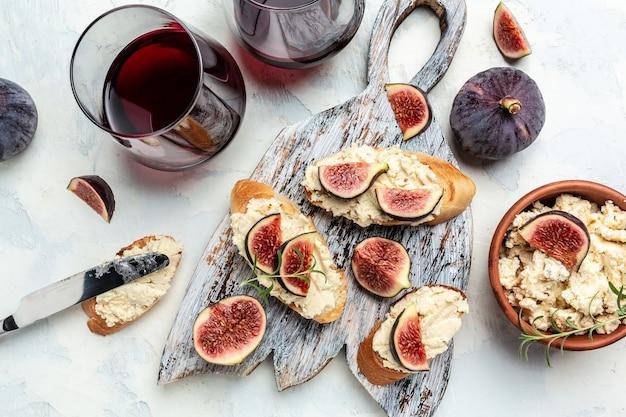 프로슈토, 크림 치즈, 무화과를 곁들인 크로스티니. 전통적인 스페인 타파스는 적포도주와 함께 전채를 설정합니다. 배너, 메뉴 레시피. 평면도