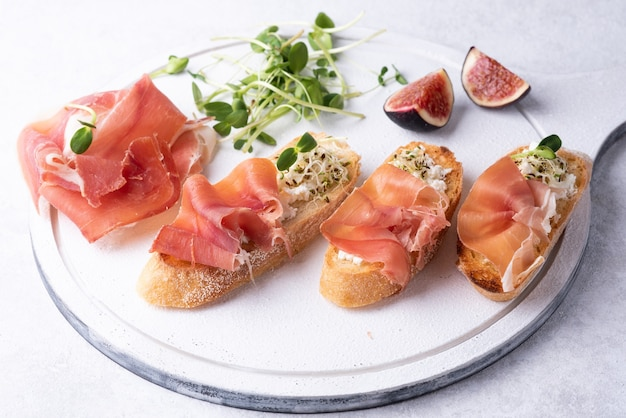 Crostini with prosciutto on a white background, antipasto of ham, ricotta and microgreens, close-up.