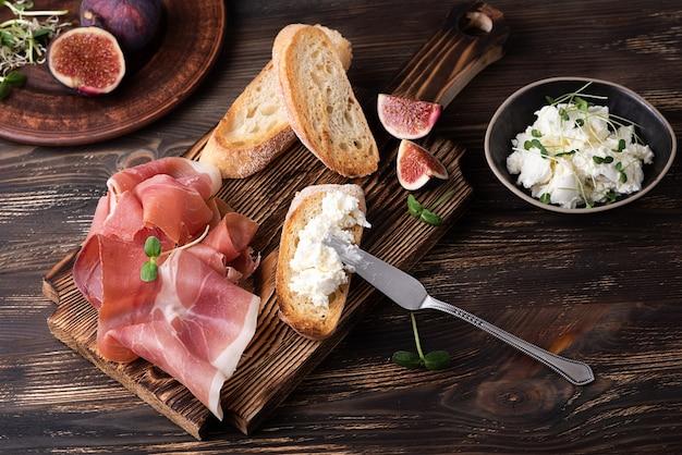 Кростини с рикоттой, прошутто и инжиром, итальянские закуски на темном деревянном фоне, деревенский стиль.
