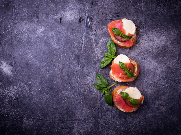 Crostini with salmon, mozarella, tomato and basil. italian starter or appetizer