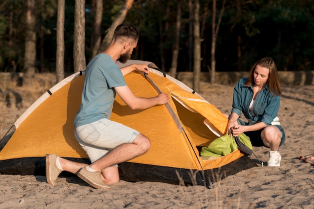 Crouching couple disassembling a camping tent