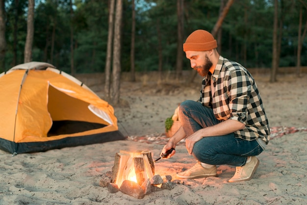 Crouching man starting a bonfire