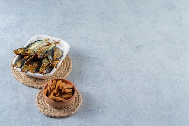 Гренки и небольшая соленая рыба, на мраморном фоне.