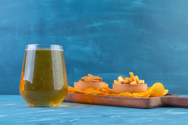 Croutons bowls and chips on a board next to beer mug , on the blue background.