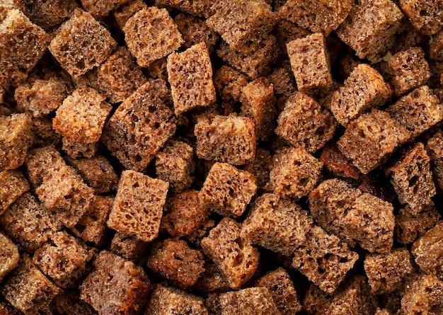 Гренки коричневый фон крупным планом, текстура из небольших кусочков сушеного хлеба. вид сверху