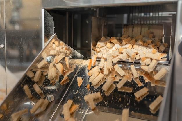 컨베이어에 크루통. 빵에서 러스크를 생산하기 위한 자동화 라인. 컨베이어 라인 머신