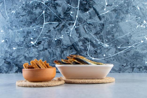 Crostini e pesciolini al sale, su fondo marmoreo.