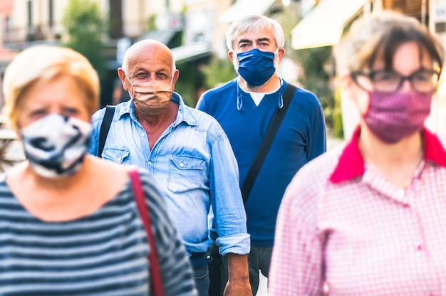 Crowd of adult citizens walking on city street with face mask in pandemy time
