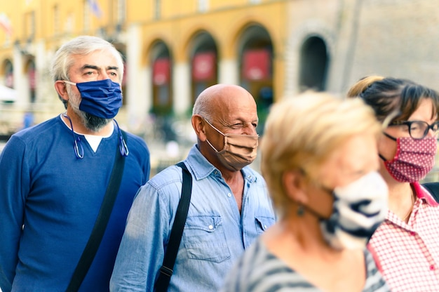 Crowd of adult people walking on city street with face mask on