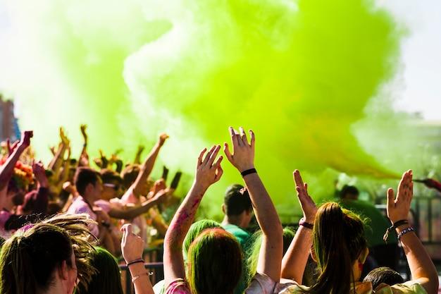 Толпа аплодирует в праздновании холи