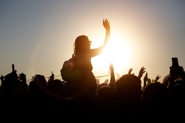 The crowd enjoys the summer music festival, sunset, the black silhouettes hands up, girl in the center