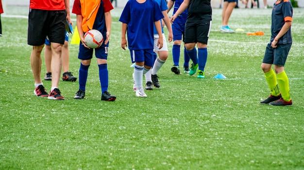 경기장의 잔디 필드에서 축구를하는 많은 어린이 아이들을 군중