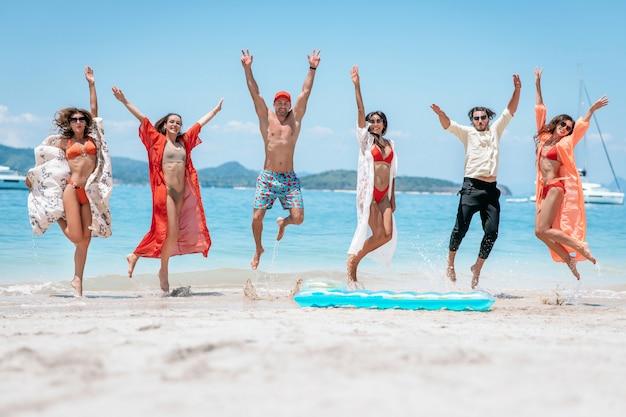 海を背景に発生した彼らの腕で砂浜でジャンプする友人の群衆