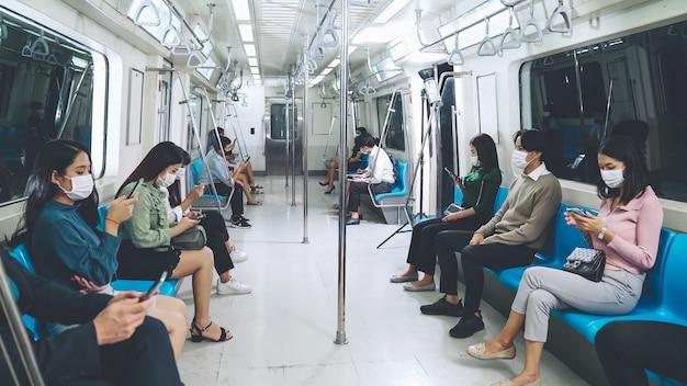 混雑した公共の地下鉄の電車の旅でフェイスマスクを着用している人々の群衆。ラッシュアワーの概念におけるコロナウイルス病またはcovid19パンデミックの発生と都市のライフスタイルの問題。