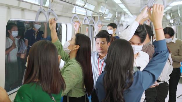 Толпа людей в масках на переполненном общественном поезде метро