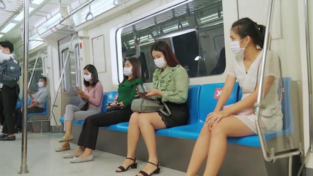 混雑した公共の地下鉄の電車の旅でフェイスマスクを着用している人々の群衆